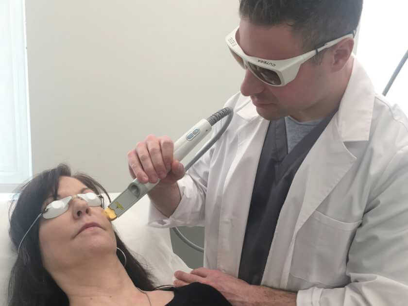 Dr. Roni Munk gives a patient a dermatological treatment